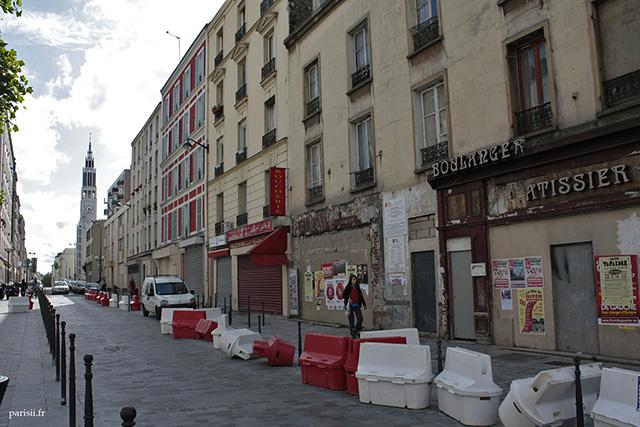 Une rue du 20e arrondissement, avec des immeubles aux portes murées