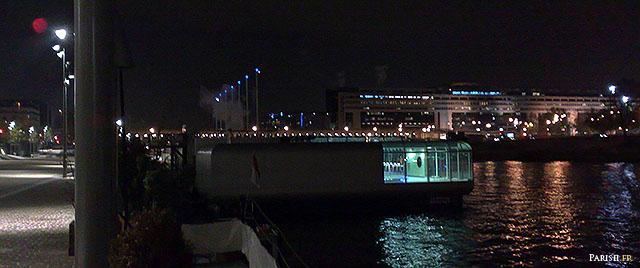 Piscine flottante sur la Seine, de nuit avec le ministère des Finances au fond