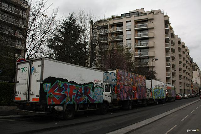 Tags sur des camions, stationnés devant des tours d'habitation parisiennes